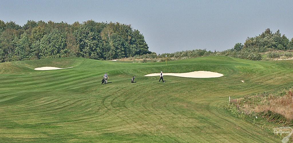 Budowa pola golfowego, galeria pól golfowych - dołek golfowy z approach i golfiści na gotowym polu golfowym Krakow Valley Golf & Country Club.