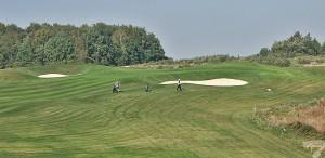 Budowa pola golfowego / galeria pól golfowych - dołek golfowy z approach i golfiści na polu golfowym Krakow Valley Golf & Country Club.