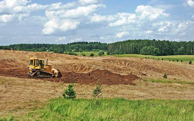 Budowa pola golfowego - wstępne kształtowanie greens i bunkrów na polu golfowym.
