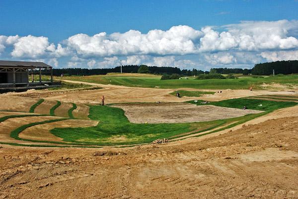 Budowa greenu golfowego: 3. Finalne kształtowanie i uprawa warstwy wegetacyjnej na green approaches, darniowanie pochyłości zapobiegające erozji wodnej.